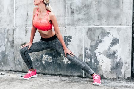 Mujer de fitness deporte de moda en ropa deportiva haciendo ejercicio físico yoga en la calle de la ciudad sobre el fondo de hormigón gris. Al aire libre ropa y calzado deportivo, estilo urbano. Foto de archivo