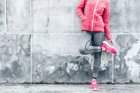 Fitness sport woman in fashion sportswear doing yoga fitness exercise in the city street over gray concrete background. Outdoor sports clothing and shoes, urban style. Archivio Fotografico