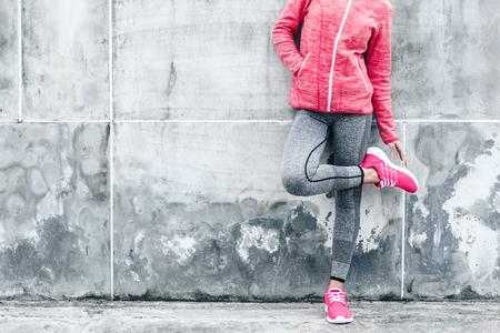 Fitness sport vrouw in de mode sportkleding doen yoga fitness oefening in de stad straat over grijze beton achtergrond. Outdoor kleding en schoenen, stedelijke stijl.