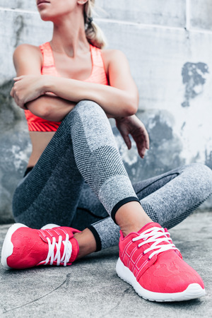Fitness sport woman in fashion sportswear doing yoga fitness exercise in the city street over gray concrete background. Outdoor sports clothing and shoes, urban style. Sneakers closeup. Stock Photo