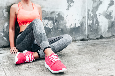 Fitness sport woman in fashion sportswear doing yoga fitness exercise in the city street over gray concrete background. Outdoor sports clothing and shoes, urban style. Sneakers closeup. Archivio Fotografico