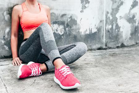 Fitness sport vrouw in de mode sportkleding doen yoga fitness oefening in de stad straat over grijze beton achtergrond. Outdoor kleding en schoenen, stedelijke stijl. Sneakers close-up.