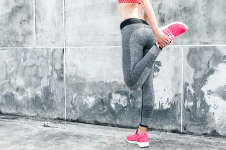 Fitness sport woman in fashion sportswear doing yoga fitness exercise in the city street over gray concrete background. Outdoor sports clothing and shoes, urban style. Standard-Bild