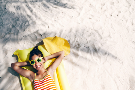 Child girl in yellow swimwear and sunglasses chilling on lilo under palm tree on sand at the beach. Tropical island. Summer holiday idyllic. Top view. Stock Photo
