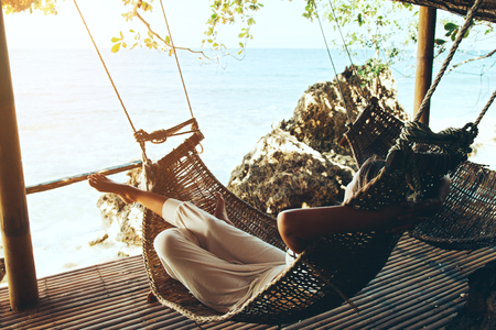 女の熱帯のビーチ、ハンモックでリラックス ホット晴れた日 写真素材 - 70918674