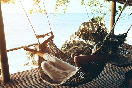 여자 열 대 해변, 뜨거운 화창한 날 그물 침대에서 휴식