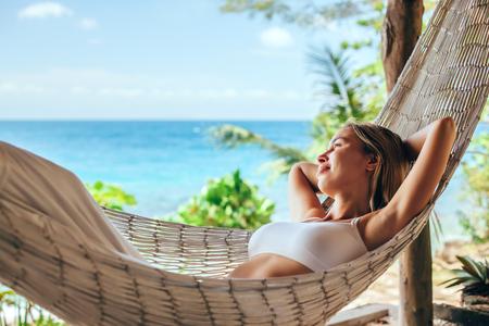 女の熱帯のビーチ、ハンモックでリラックス ホット晴れた日 写真素材 - 70918675