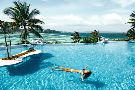 Kind zwemmen in de luxe infinity pool met uitzicht op zee. Zomervakantie idyllisch in het hotel. Filipijnen, Boracay eiland.