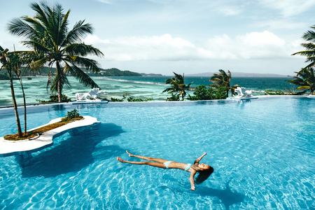 Child swimming in the luxury infinity pool with ocean view. Summer holiday idyllic in hotel. Philippines, Boracay island. Archivio Fotografico