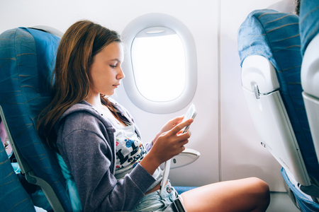 10 years old girl sitting inside airplane and playing on tablet Stock Photo