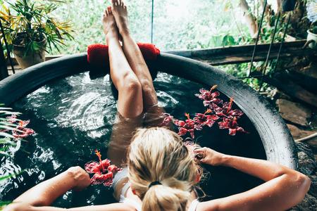 Vrouw ontspannen in ronde openlucht bad met tropische bloemen. Biologische huidverzorging in kawa warm bad in luxe spa resort.