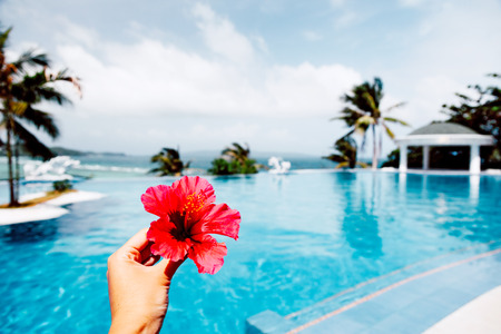 Tropical flower in hand over luxury infinity pool with ocean view. Summer holiday idyllic in hotel. Philippines, Boracay island.