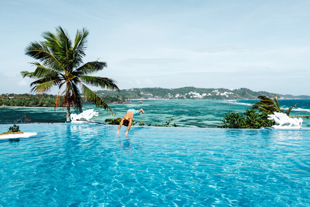 Guy jumping in the luxury infinity pool with ocean view. Summer holiday idyllic in hotel. Philippines, Boracay island.