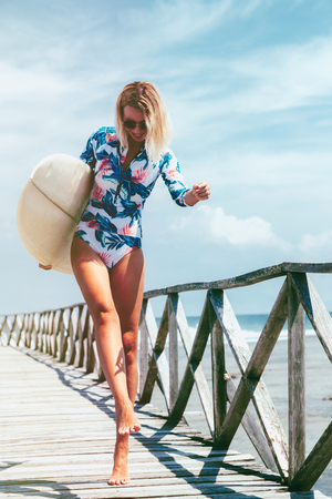 Surfer girl in sport swimwear and sunglasses posing with surfboard on the beach. Active lifestyle and summer vacations. Standard-Bild