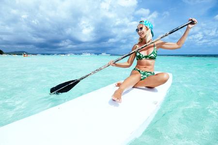 若い女性は、熱帯のビーチでの SUP ボードにパドリングします。パドルボードとアクティブな夏の休暇。