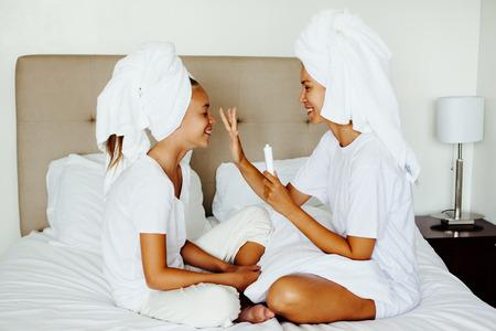 ママとシャワーの後の寝室でリラックスできる 10 歳 preteen 子供。彼女の娘の顔にクリームを傷母を適用します。家族の美容トリートメント。朝の手