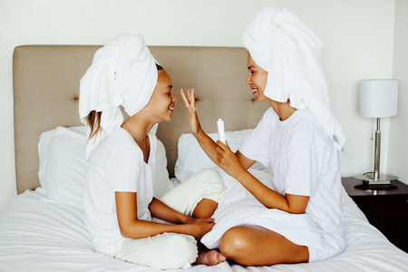 Mom and her 10 years old preteen child relaxing in the bedroom after shower. Mother applying blemish cream on her daughter face. Family beauty treatment. Morning care routine. Teenage skin problems.