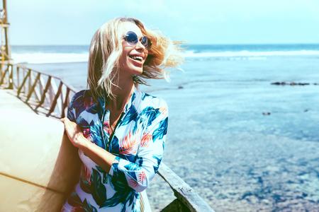 chica surfista en traje de baño y gafas de sol del deporte que presenta con la tabla de surf en la playa. Estilo de vida activo y las vacaciones de verano.