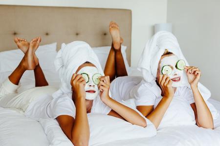 Moeder en haar 10 jaar oude dochter preteen chillen in de slaapkamer en het maken van klei gezichtsmasker. Moeder met kind doet schoonheidsbehandeling bij elkaar. Morning huidverzorging routine.