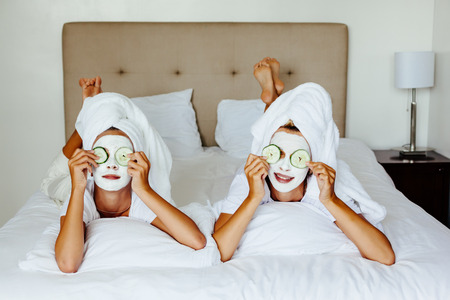 Mom and her 10 years old preteen daughter chilling in the bedroom and making clay facial mask. Mother with child doing beauty treatment together. Morning skin care routine. Archivio Fotografico