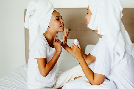 blemish: Mom and her 10 years old preteen child relaxing in the bedroom after shower. Mother applying blemish cream on her daughter face. Family beauty treatment. Morning care routine. Teenage skin problems.