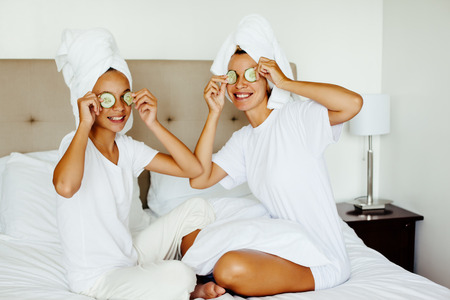 cucumbers: Mom and her 10 years old preteen daughter chilling in the bedroom and making clay facial mask. Mother with child doing beauty treatment together. Morning skin care routine. Stock Photo
