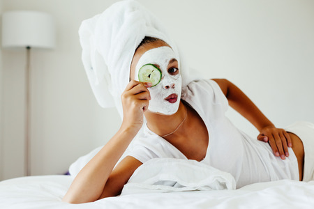 blemish: 10 years old preteen chilling in the bedroom and making clay facial mask. Teenage girl doing anti blemish skin treatment. Morning skin care routine.