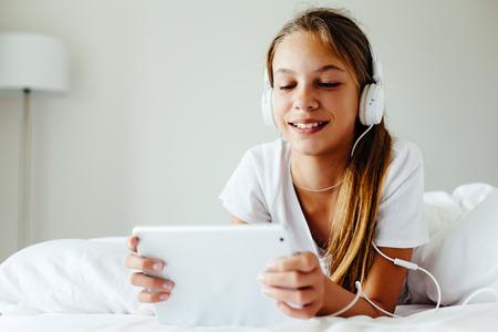 10 歳の子は、タブレット pc を使用して。事前に十代の少女、ベッドで横になっているヘッドフォンで音楽を聴くと、ソーシャル ネットワークを参照