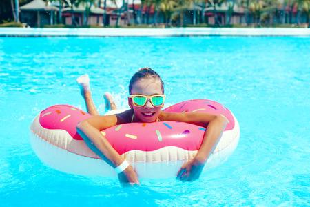 fille Tween détente sur le lilo beignet dans la piscine de la station en Thaïlande Banque d'images