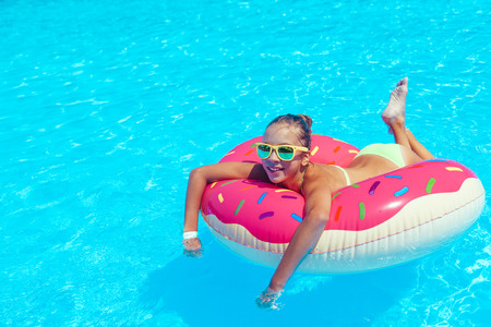 10 years old: Tween girl relaxing on the inflatable ring in resort pool in Thailand