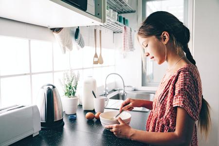 10 歳の子供女の子のカジュアルなライフ スタイル写真シリーズのキッチンで料理します。子供が朝食を一人で作る。居心地の良い家庭的なシーン。