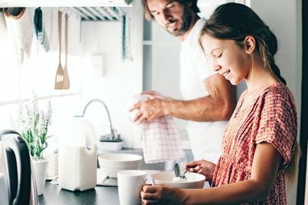 Tato z jego 10 letni dzieciak dziewczyna gotowania w kuchni, na co dzień styl życia serii zdjęć. Dziecko czyni śniadanie z rodzicem razem. Przytulne domową sceny.