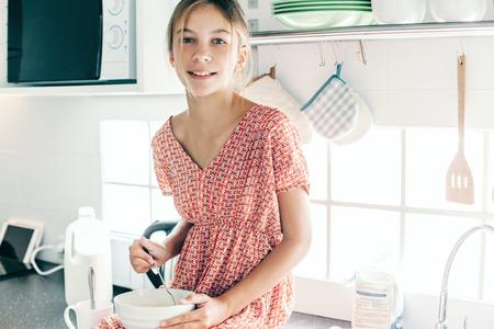 10 세 아이 소녀 부엌, 캐주얼 라이프 스타일 사진 시리즈에서 요리. 아침 식사를 혼자하는 아이. 아늑한 가정적인 장면.