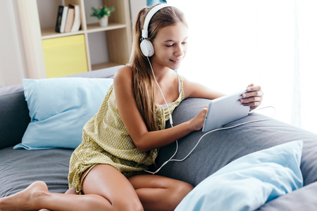 10 years old tween girl relaxing on a couch, listening to music in headphones and playing with tablet pc. Child chilling on the sofa in living room. Reklamní fotografie