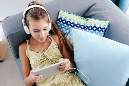 10 ans tween girl se détendre sur un canapé, écouter de la musique dans les écouteurs et jouer avec tablet pc. Enfant se détendre sur le canapé dans le salon. Banque d'images