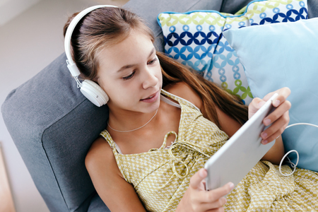 pre adolescent girl: 10 years old tween girl relaxing on a couch, listening to music in headphones and playing with tablet pc. Child chilling on the sofa in living room. Stock Photo