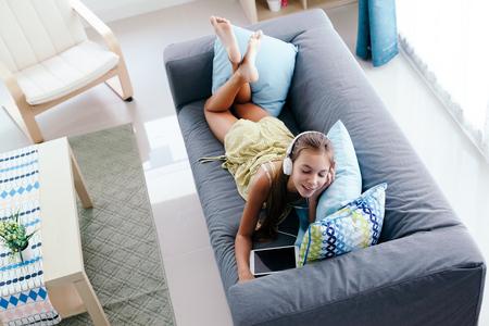 10 ans entre fille de détente sur un canapé, écouter de la musique dans les écouteurs et jouer avec tablette pc. Enfant refroidissement sur le canapé dans le salon. Banque d'images