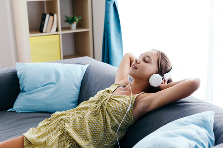 10 years old tween girl relaxing on a couch, listening to music in headphones and playing with tablet pc. Child chilling on the sofa in living room. Banque d'images