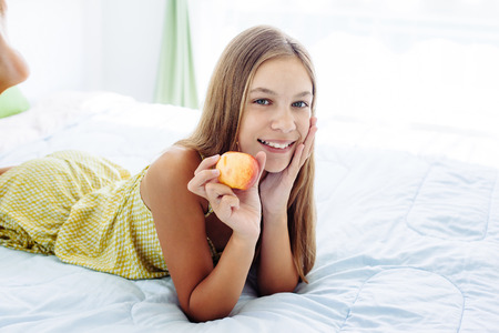 comforted: 10 years old pre teen girl eating apple while relaxing in bedroom. Healthy food for breakfast.