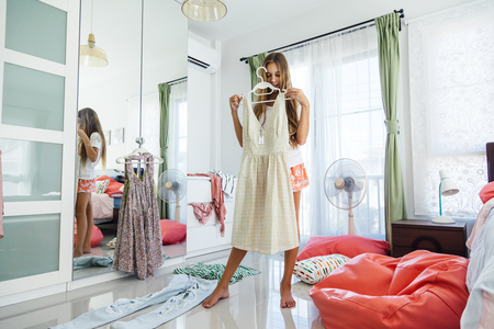 10 years old pre teen girl choosing outfit in her closet. Messy in the bedroom, clotning on the floor. Teenager is dressing up and singing in the morning. Stock Photo