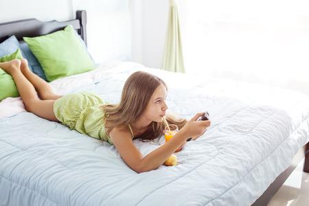 10 jaar oud tiener meisje drinken jus d'orange tijdens het kijken naar tv in hotel slaapkamer alleen Stockfoto - 72660855