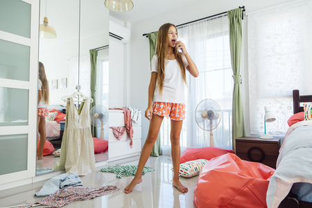 10 ans pré adolescente choisissant tenue dans son placard. Messy dans la chambre, clotning sur le sol. Adolescent est habiller et chantant dans la matinée.