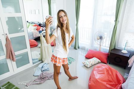 10 년 이전 사춘기 소녀 그녀의 옷장에서 옷을 선택합니다. 침실에서 어리석은 바닥에 clotning. 십대 소녀는 차려 입과 아침에 셀카를 데리고 간다.