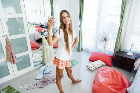 10 years old pre teen girl choosing outfit in her closet. Messy in the bedroom, clotning on the floor. Teenager is dressing up and taking selfie in the morning.