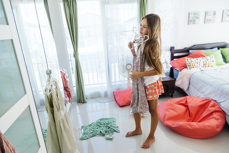 10 years old pre teen girl choosing outfit in her closet. Messy in the bedroom, clotning on the floor. Teenager is dressing up and singing in the morning. Фото со стока