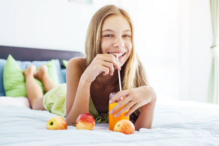 comforted: 10 years old pre teen girl drinking orange juice while relaxing in bedroom. Healthy food for breakfast.