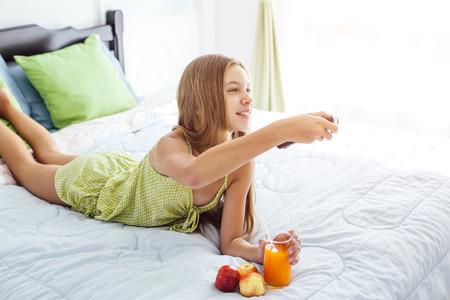 10 jaar oud tiener meisje drinken jus d'orange tijdens het kijken naar tv in hotel slaapkamer alleen Stockfoto