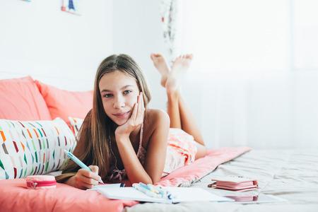 10-12 Jahre alt pre teen Mädchen schriftlich Tagebuch in rosa Schlafzimmer Standard-Bild - 72681041