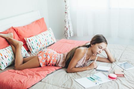 ピンクのベッドルームで学校の宿題をやって 10-12 歳前の十代の少女