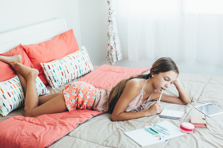 10 years girls: 10-12 years old pre teen girl doing school homework in pink bedroom